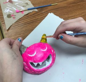 hands painting a ceramic monster mask