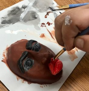 hand painting a small ceramic mask