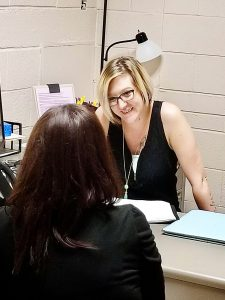 Peer Support Specialist Jessie Taylor talks to a client at her desk in Pratt Kansas